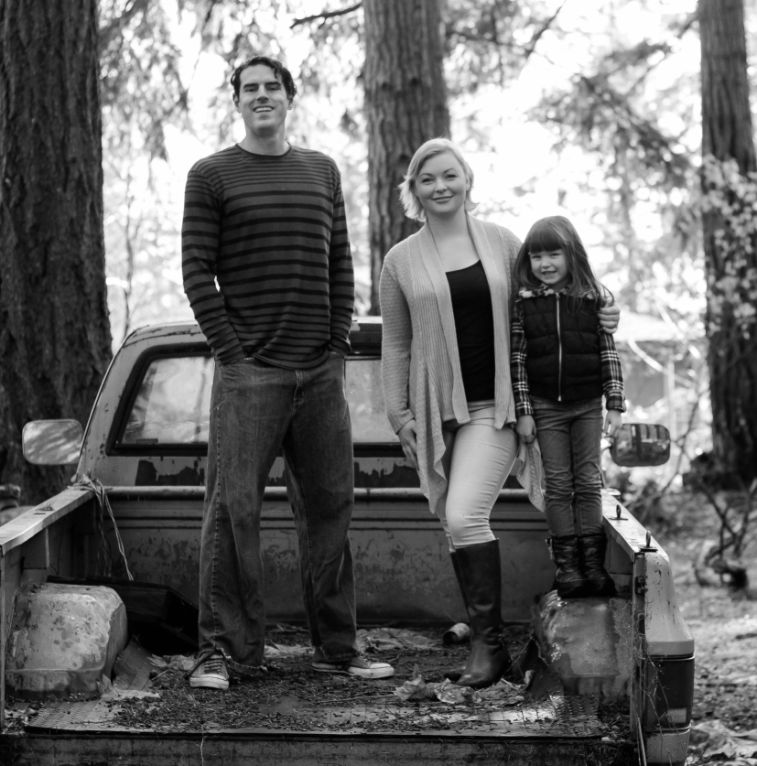 two parents and daughter standing in the back of a pick up truck