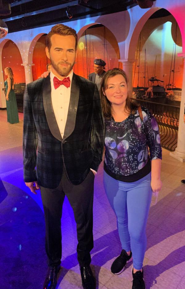 woman standing next to Ryan Reynolds wax figure at Madame Tussauds.