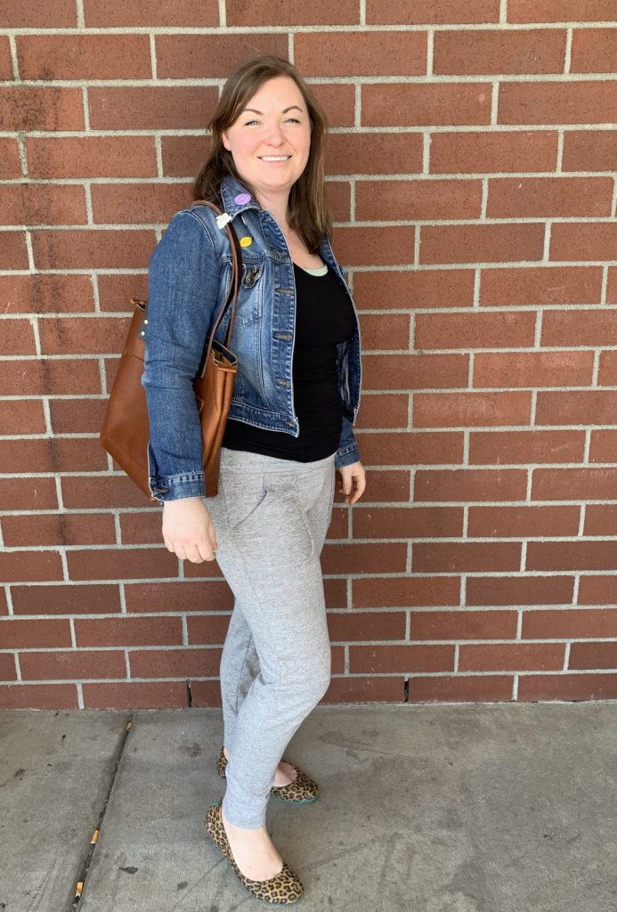 Woman in denim jacket standing in front of a brick wall.